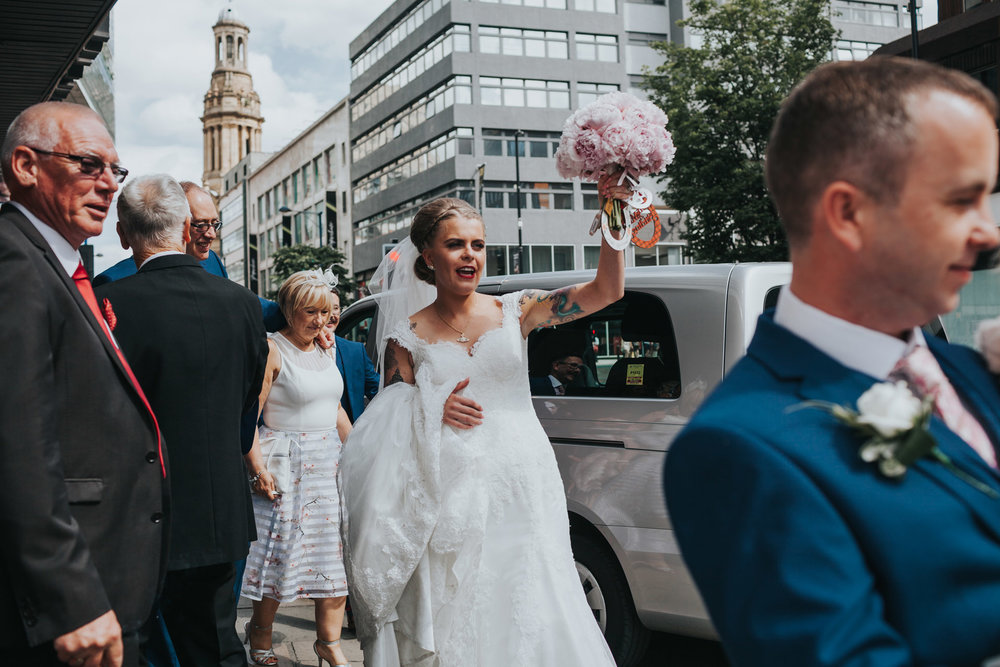 Bride exits Manchester wedding venue holding her bouquet in the air.