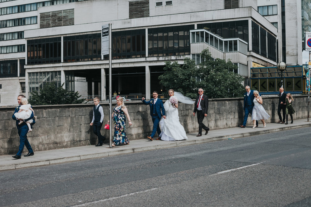 Bride and Groom walk with wedding guests through the streets on Manchester.