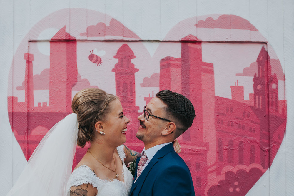 Cool bride and groom in front of Manchester graffiti.