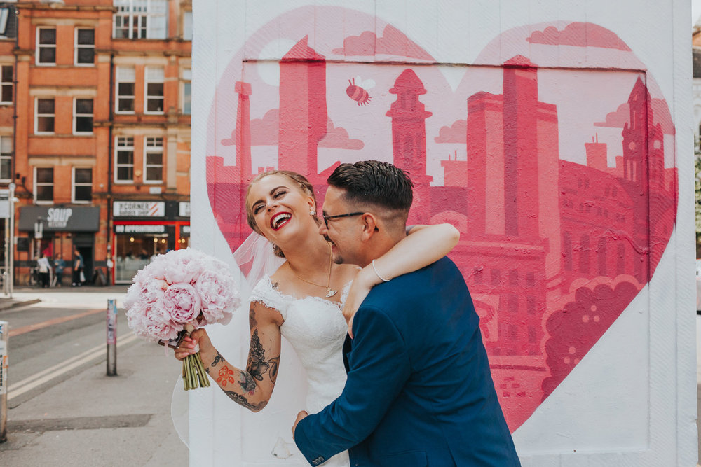 Bride and groom messing around on their wedding day in the Northern Quarter, Manchester.