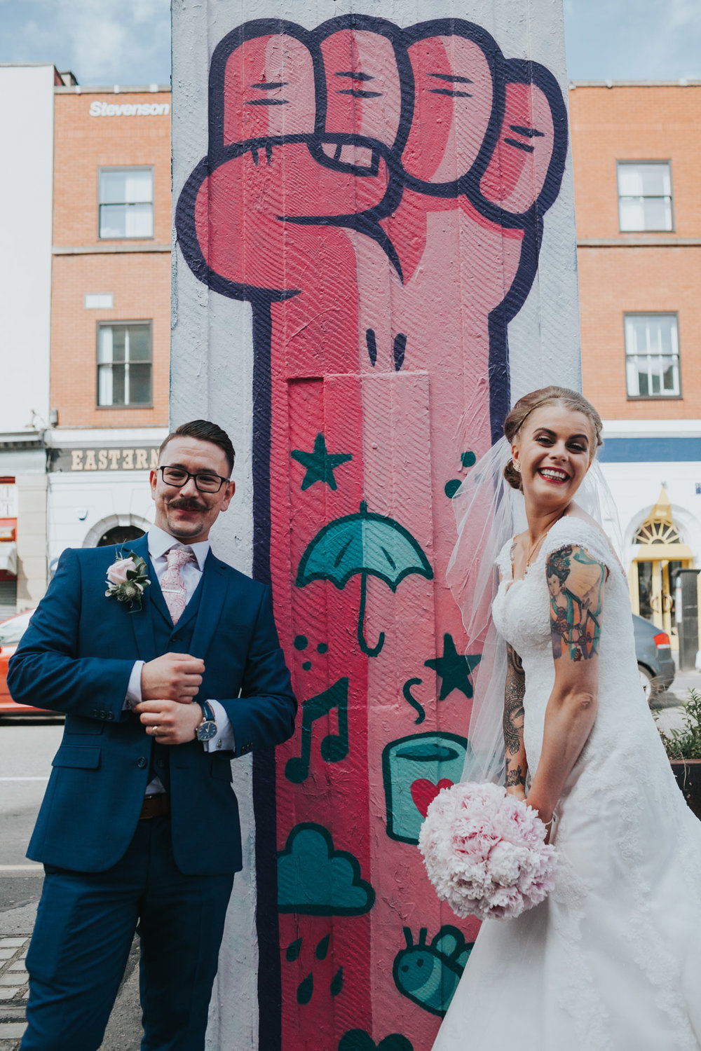 Bride and Groom smile in front of pink power to the people street art in Stevenson Square, Manchester.