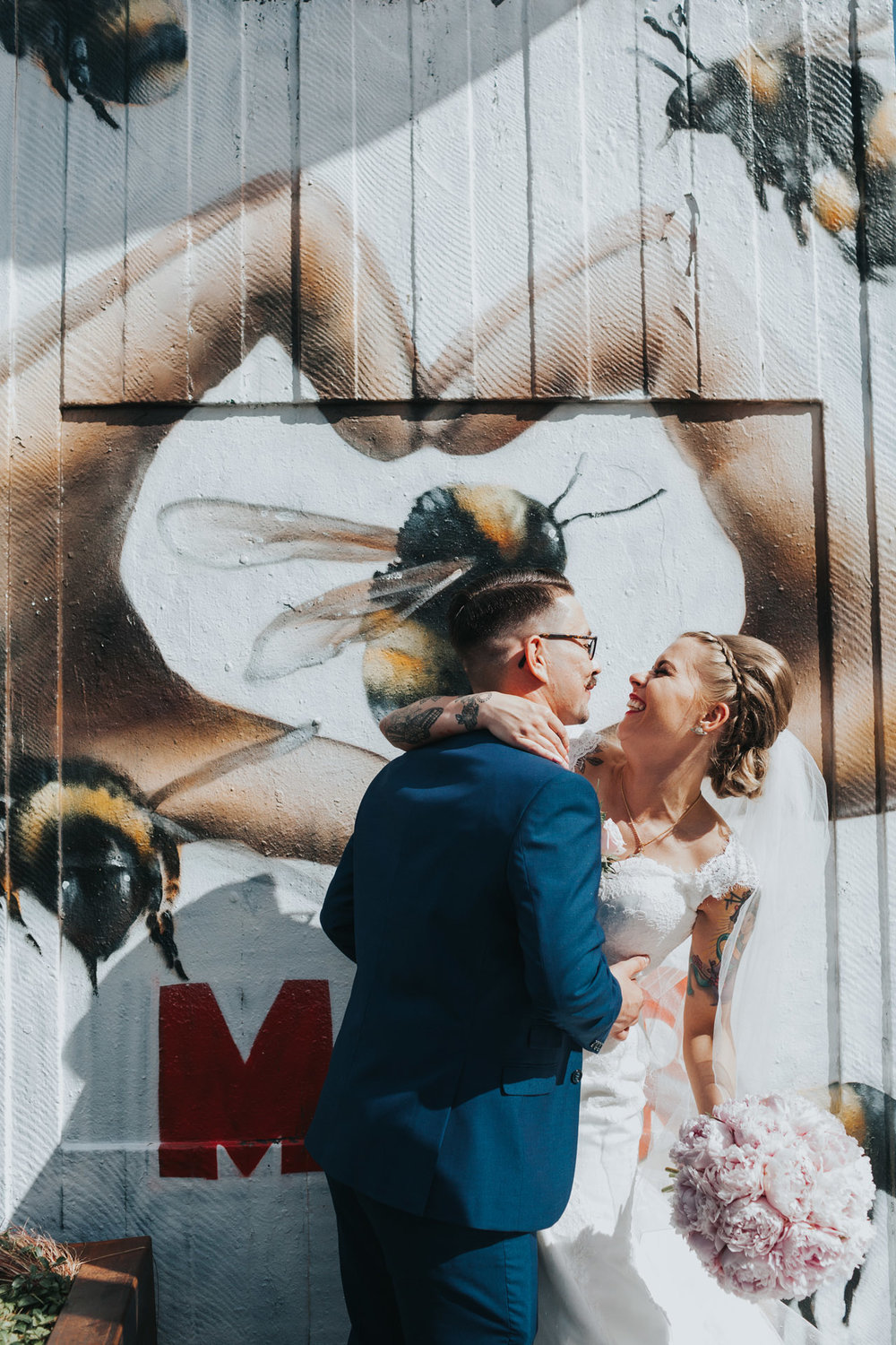 Bride and Groom pose in front of Manchester Bee Hand Heart Street art in Stevenson Square, The Northern Quarter, Manchester.