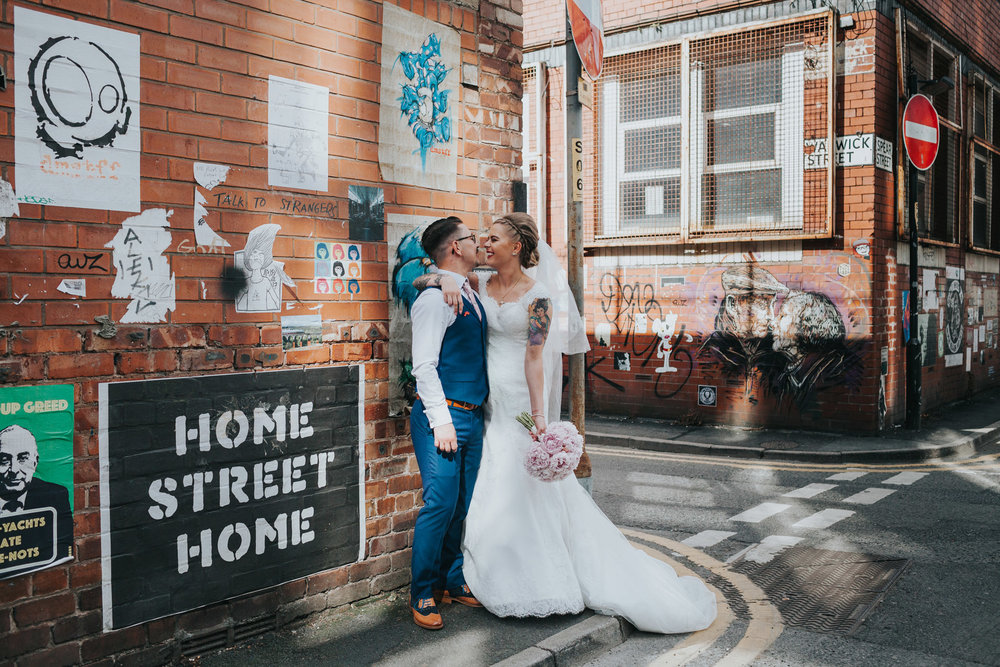 Couple stand laughing together for wedding photographs in front of various street art at Warwick Street, Manchester.