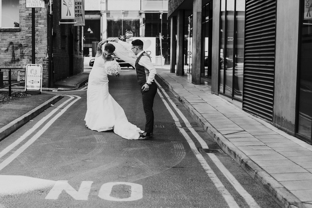 Black and white photograph of couple dance in Manchester back alley on their wedding day.