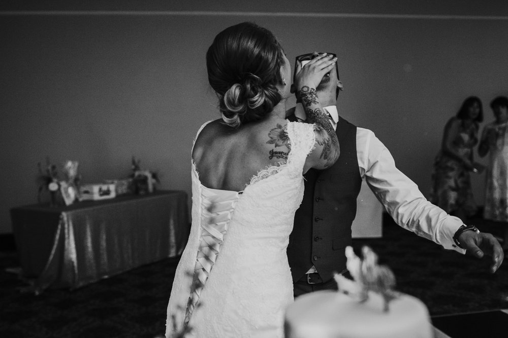 Bride feeds cake to groom. Image in black and white.