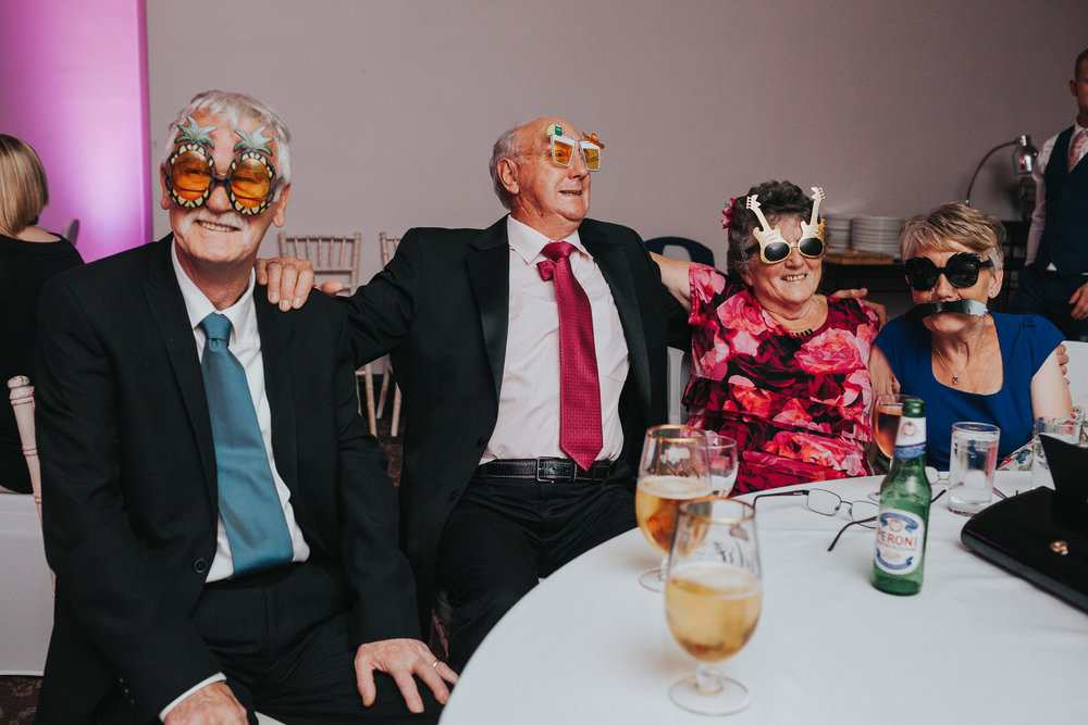 Wedding guests sit at table wearing wacky glasses at Manchester Wedding.