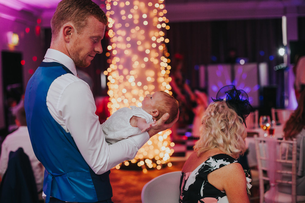 Man holding new born baby at wedding party.