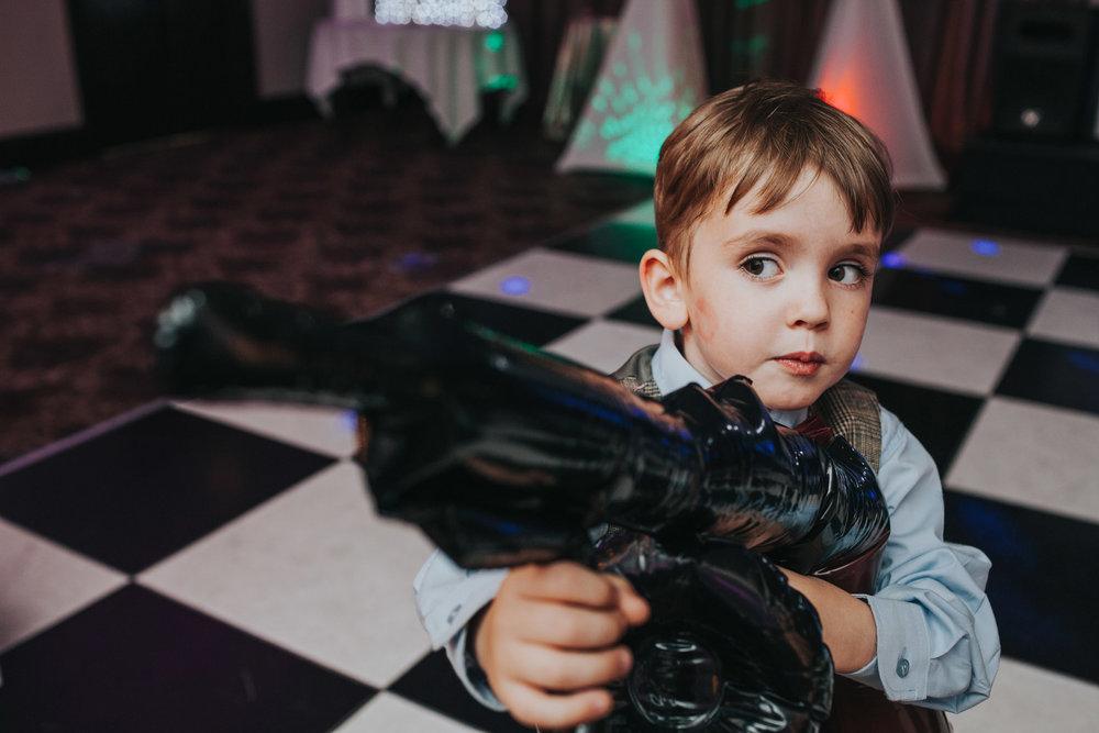 Child holding blow up machine gun at Manchester wedding party.