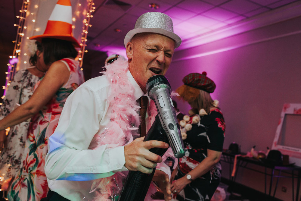 Man sings into blow up mic at wedding party.