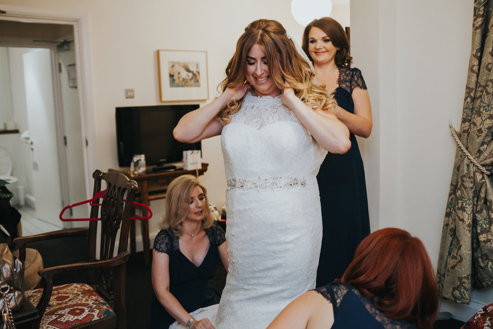 Bride gets into her wedding dress in her hotel room in merseyside.