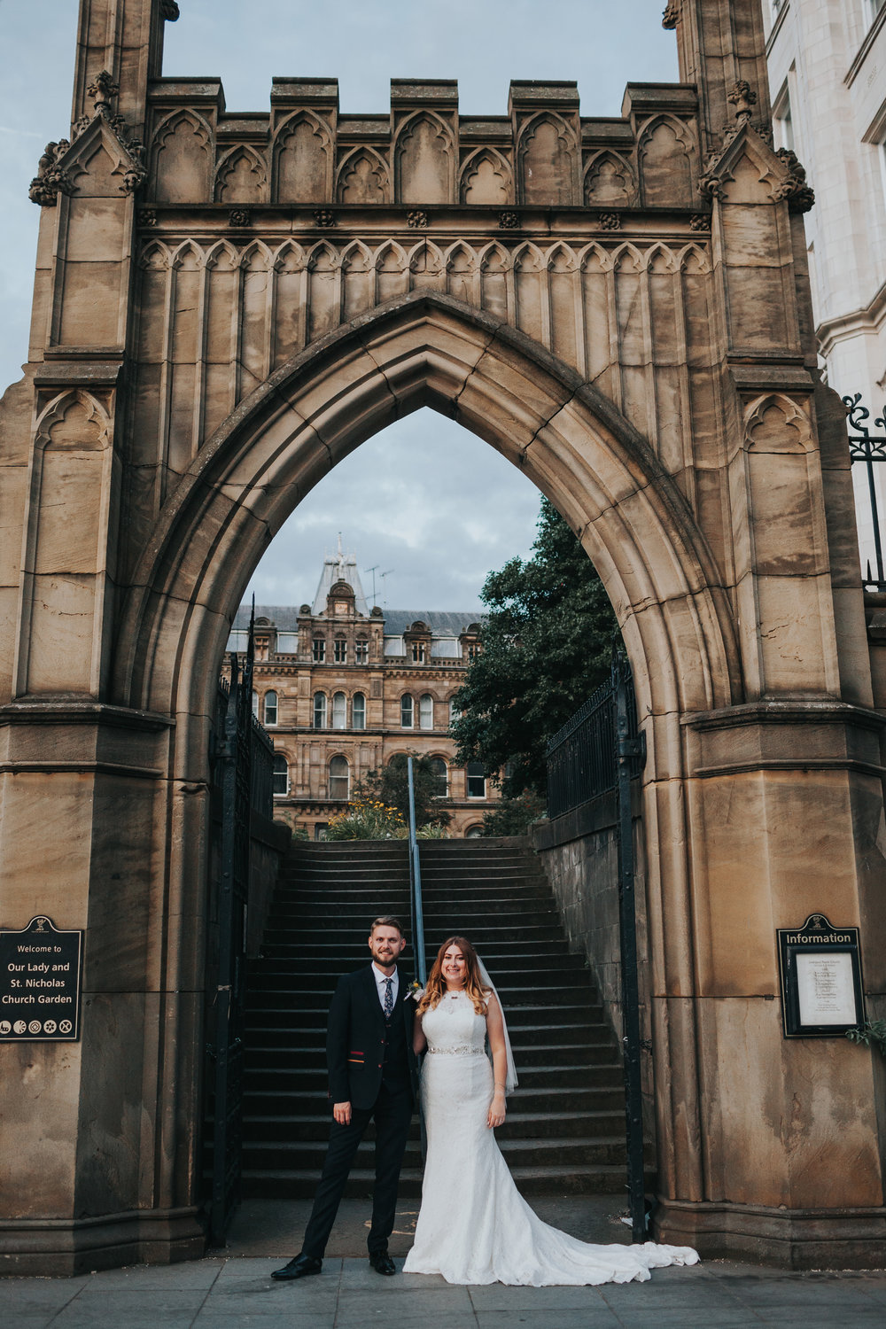Bride and Groom stand together under grand archway, Liverpool.