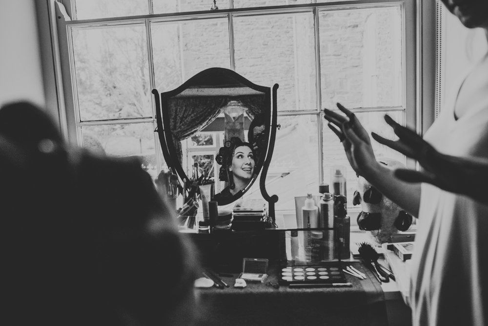 The brides reflection in the mirror as she smiles at her friend, photograph in black and white.