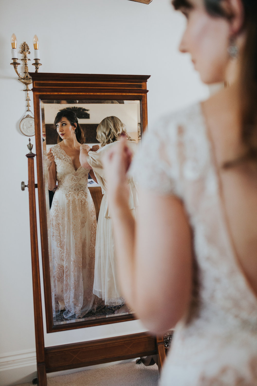 Bride standing in front of the mirror in her wedding dress.