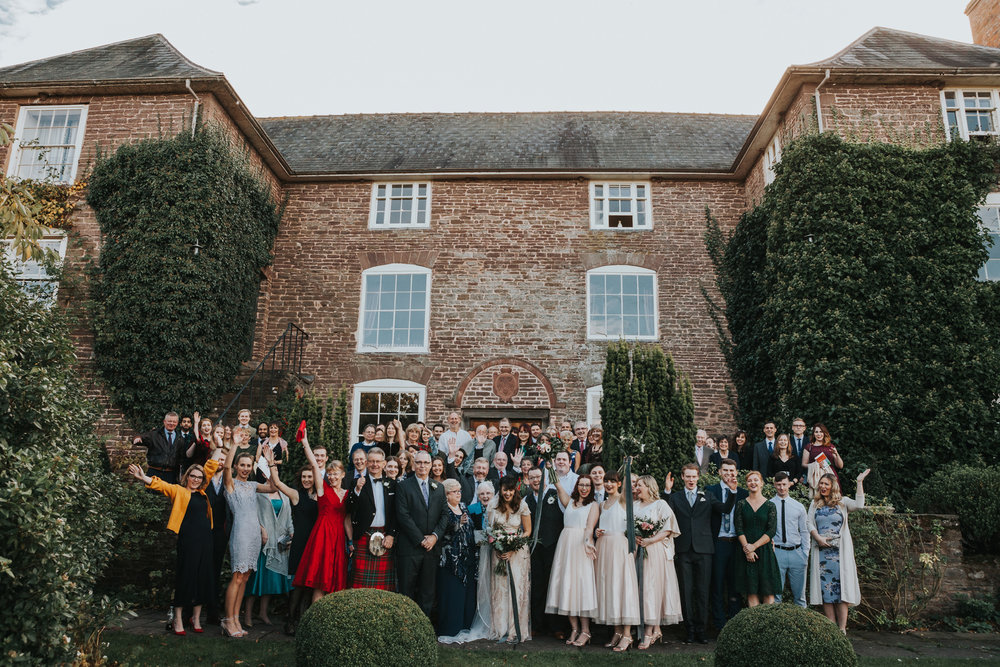 Group photograph of all wedding guests in front of the main house at Dewsall Court.