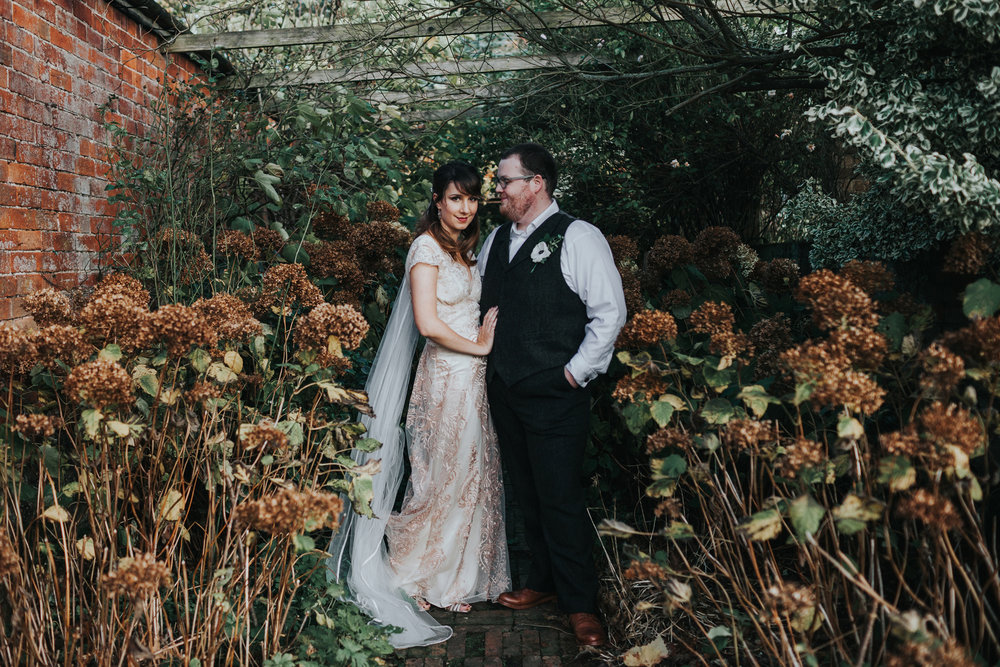 Bride and groom stand together in a sea of browning hydrangeas.
