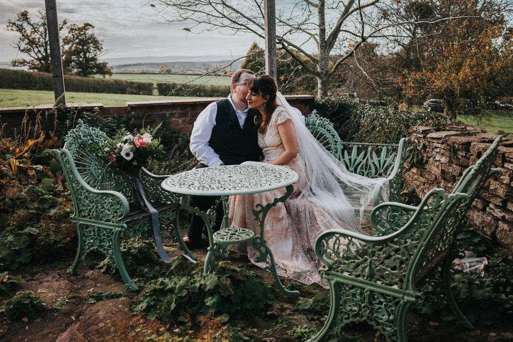 Bride and groom share a moment on teal iron chairs at Dewsall Court.