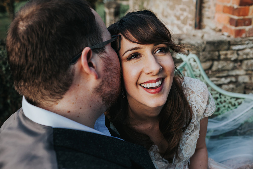 Bride smiles as groom whispers something in her ear.
