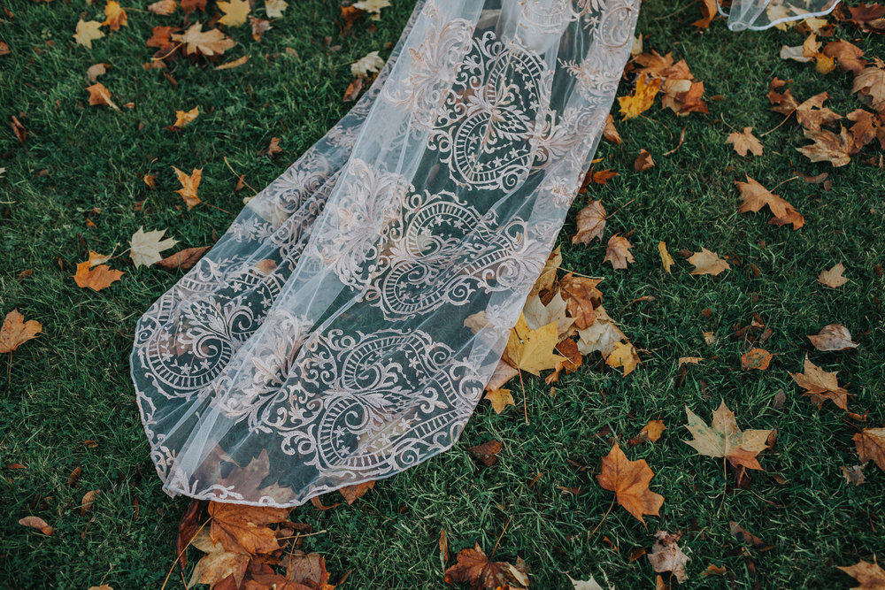 Brides dress trails in autumn leaves.