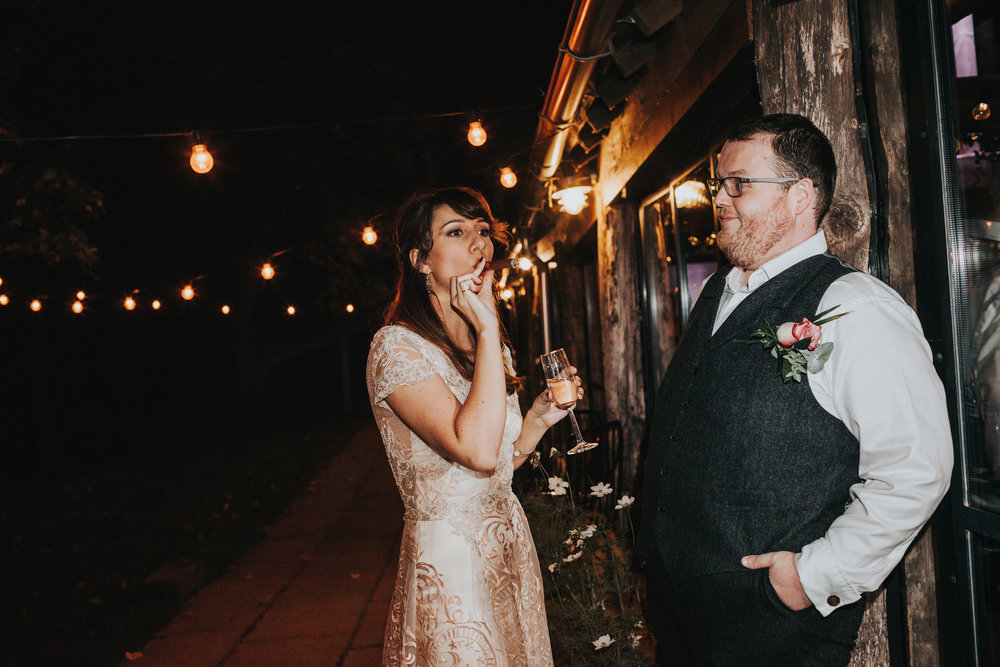 Bride and groom share a cigar.
