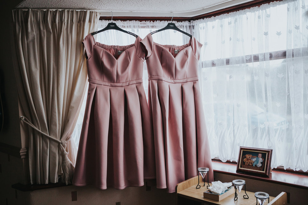 Bridesmaid dresses hanging in the window.