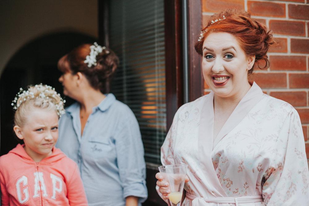 Bride looking excited, flower girl in background looking unsure.