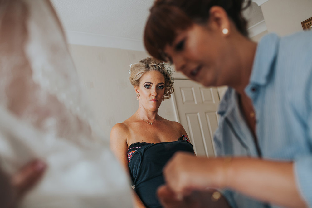 Bridesmaid watching bride getting ready.