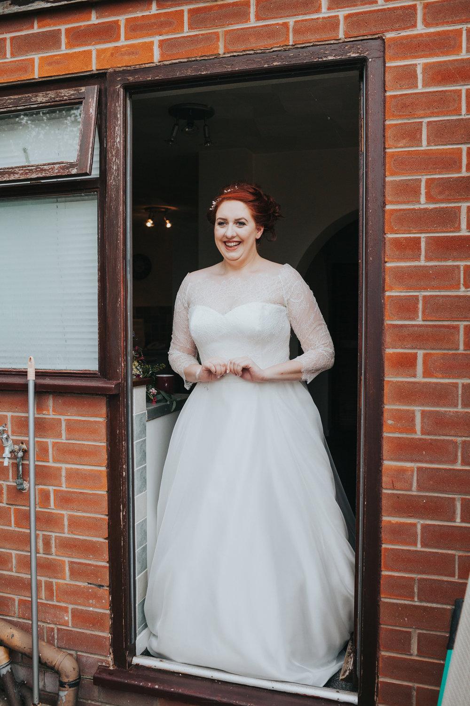 Bride standing at back door in her dress.