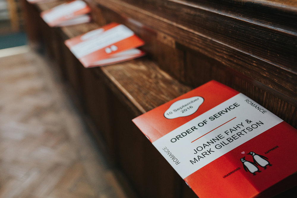 Penguin Order or Service lined up on church pew.