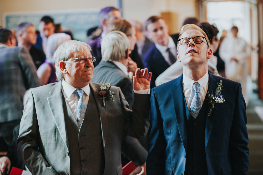 Grooms Dad comforts groom as he stands at the end of the aisle waiting for bride.