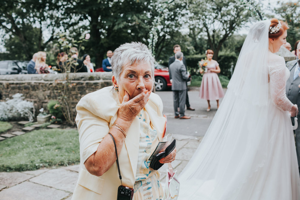 Wedding Guest with hand over her face looking guilty.