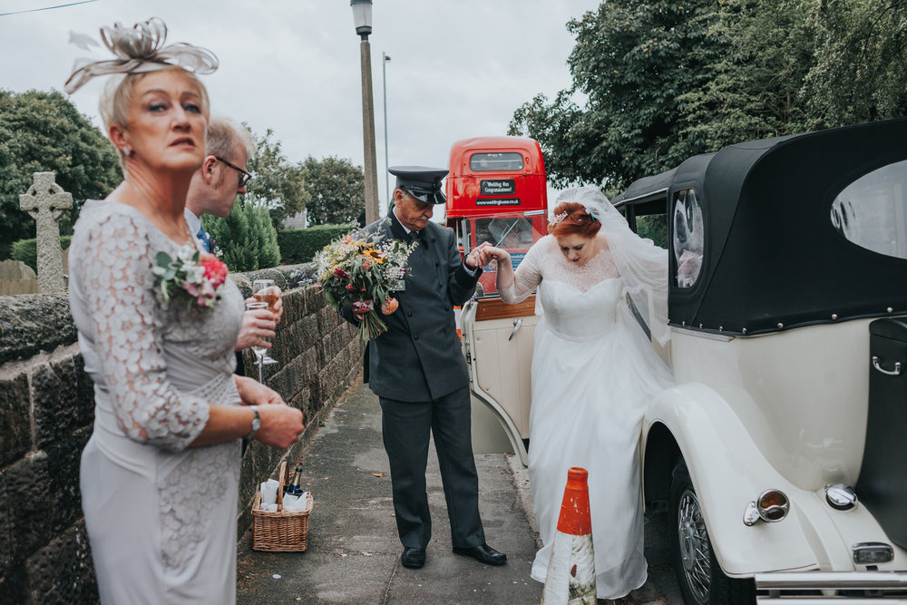 Brides mother waits outside wedding car as bride is helped into it by driver, big red bus in the back ground.