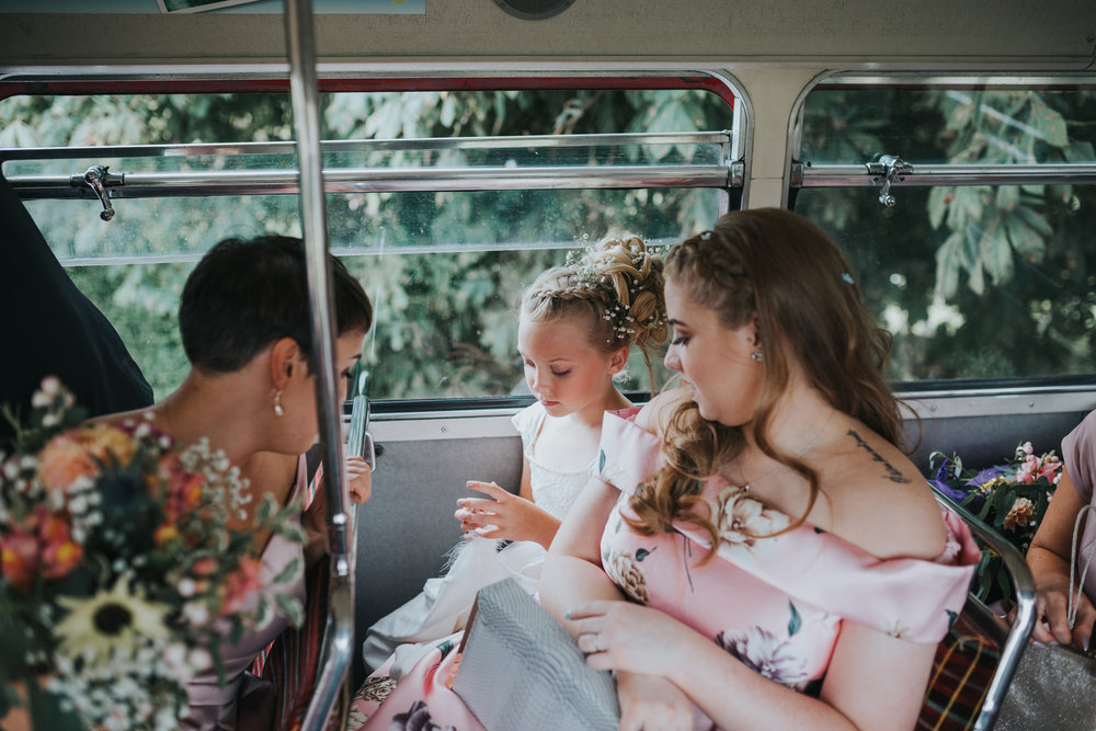 Flower girl sitting on the top deck of the wedding bus.