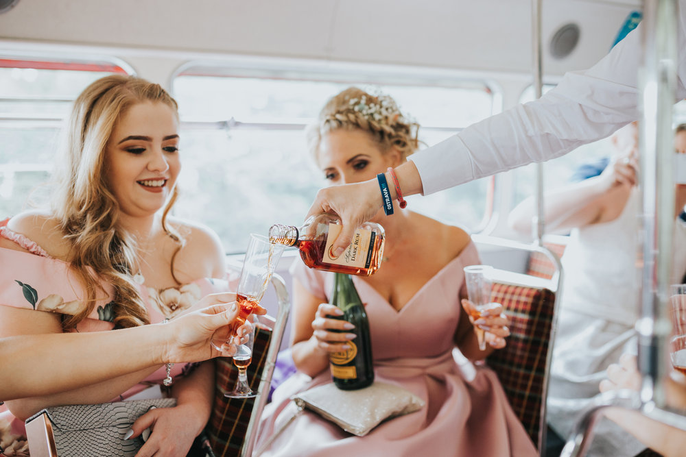 Guests pour some hard liquor on the top deck of the wedding bus.