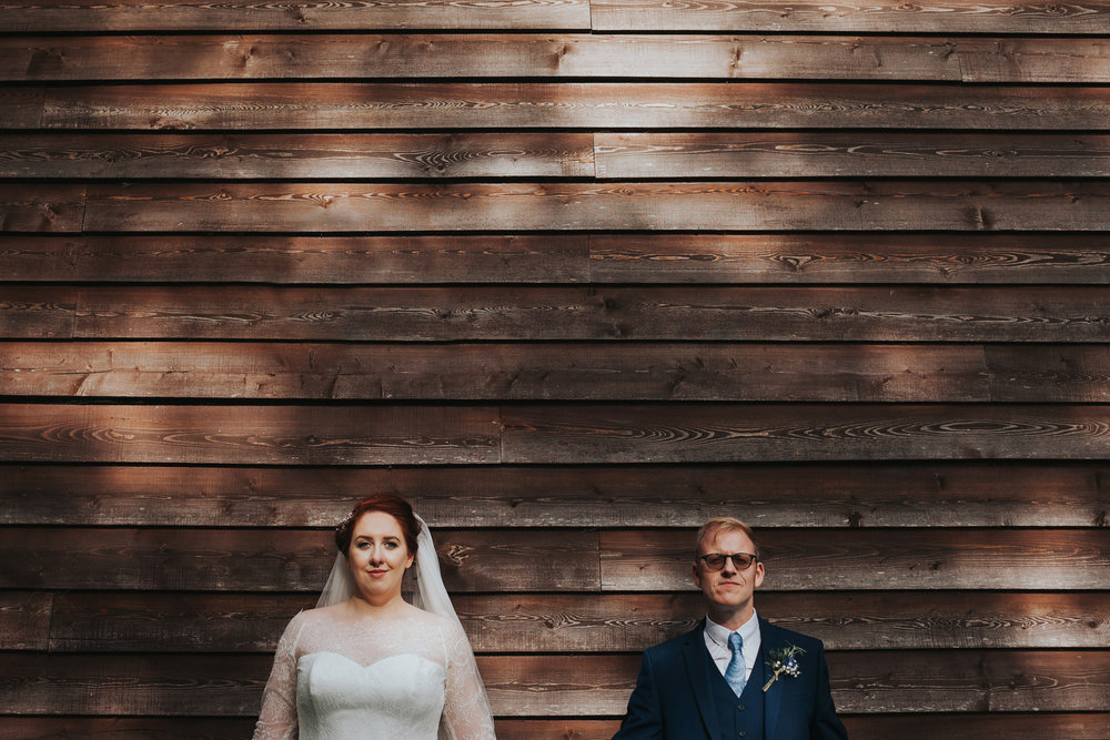 Bride and Groom pose in dappled light against wooden wall at Trafford Hall, Liverpool.
