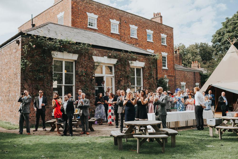 Wedding guests enjoy the garden at Trafford hall.