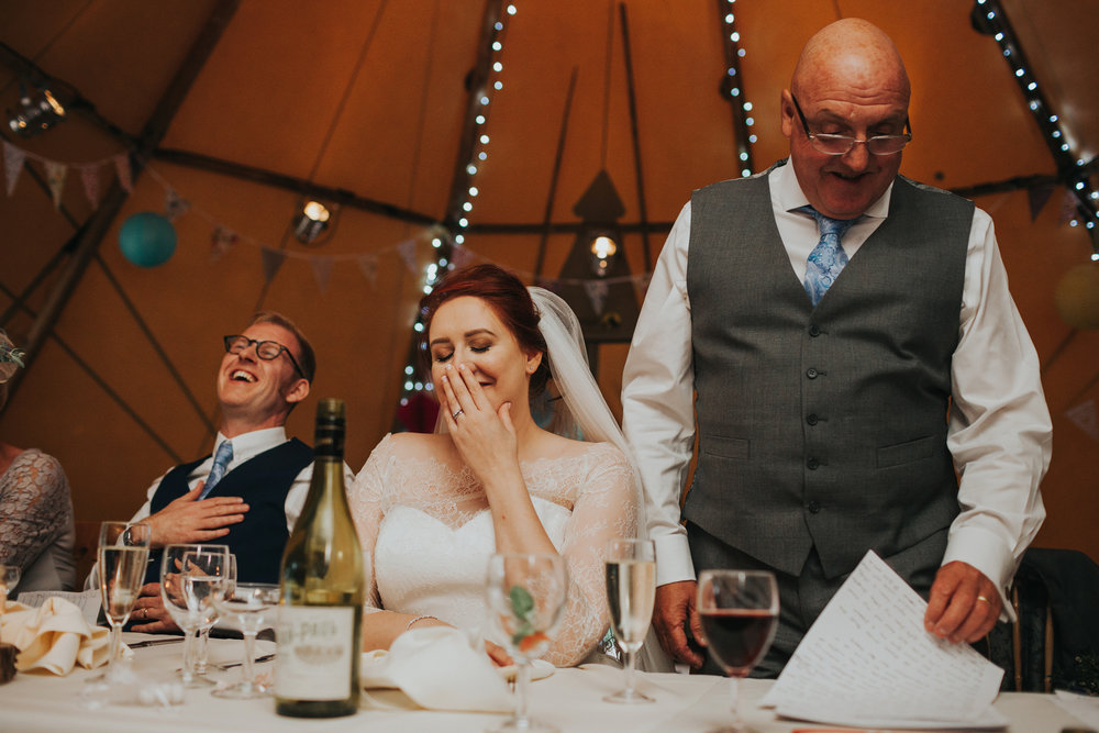 Bride and groom laughing at speech.