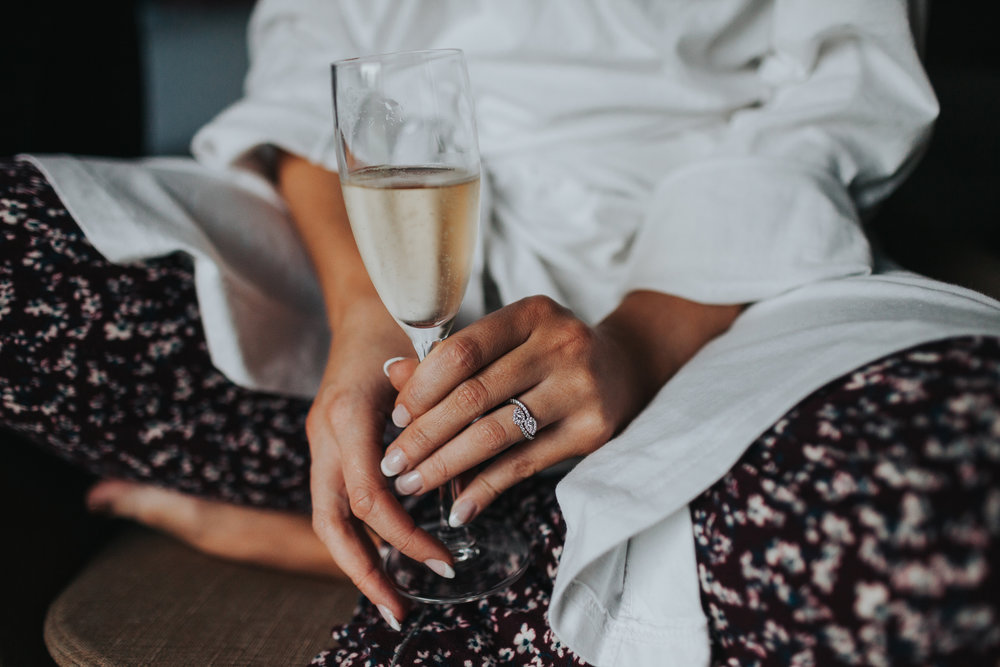 Bride holding champagne glass with her engagement ring showing.