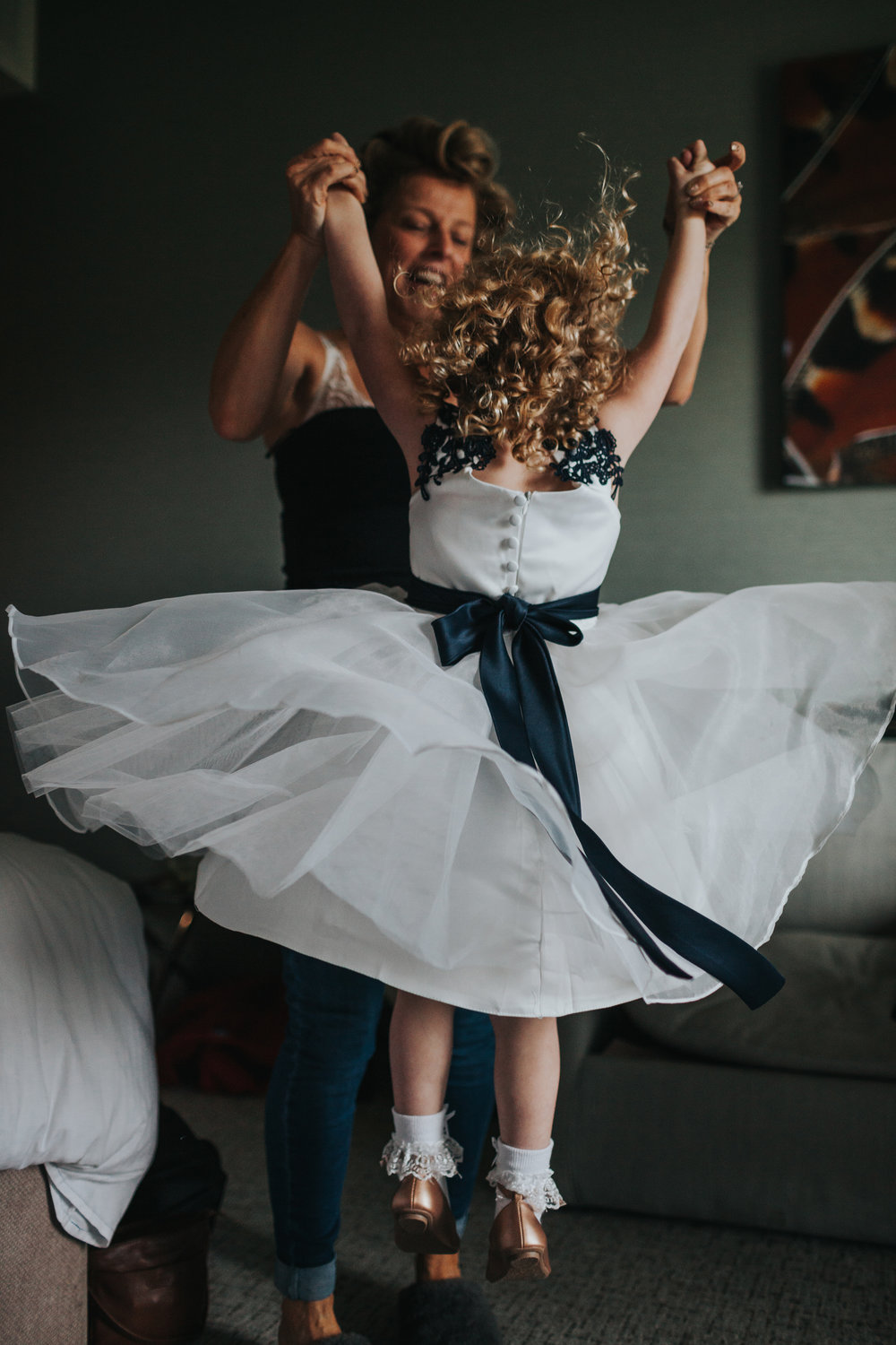 Flower girl jumping with Mother of the bride.