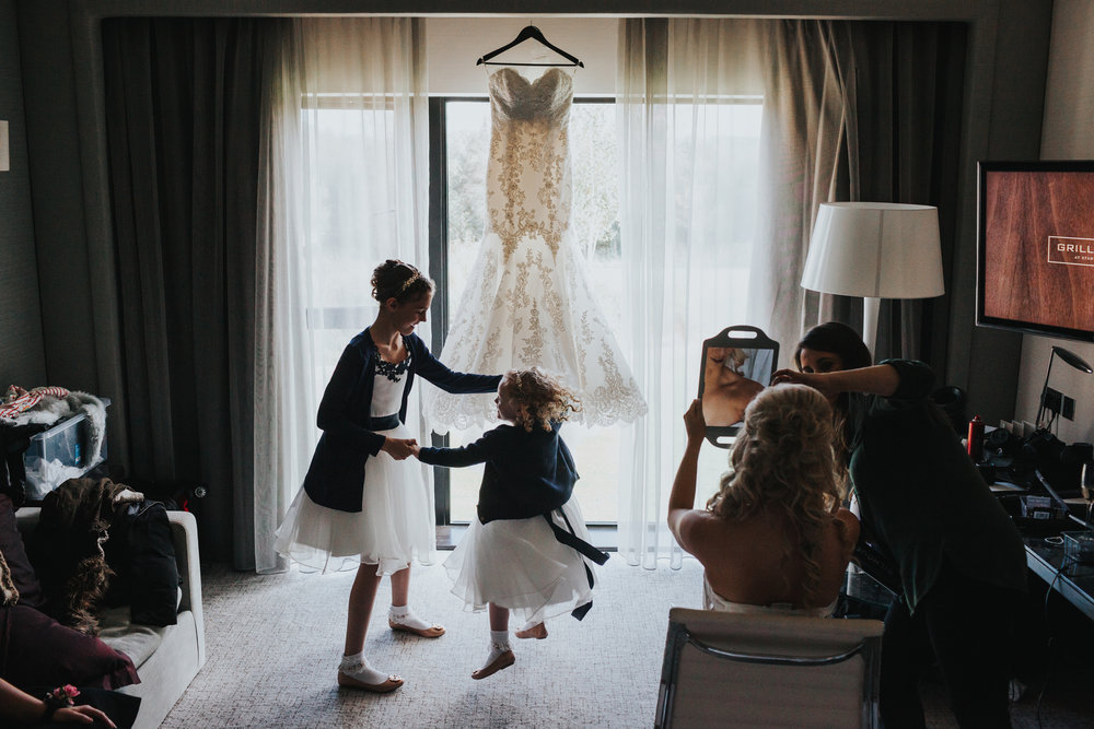 Flower girls dance in front of wedding dress as bride has the finishing touches to her make up done.