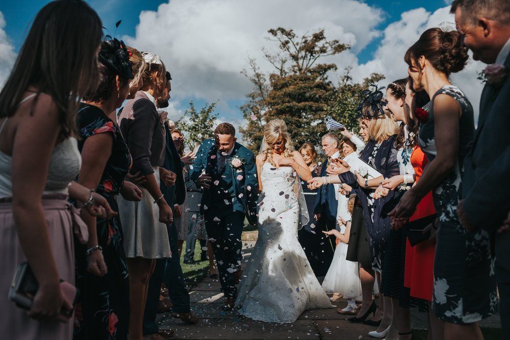 Bride and groom walk between guests as wedding guests throw confetti at them.