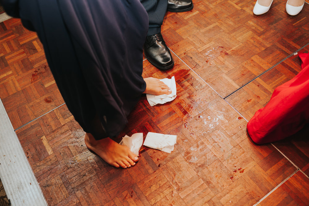 Bridesmaid uses napkin feet to wipe up the floor.