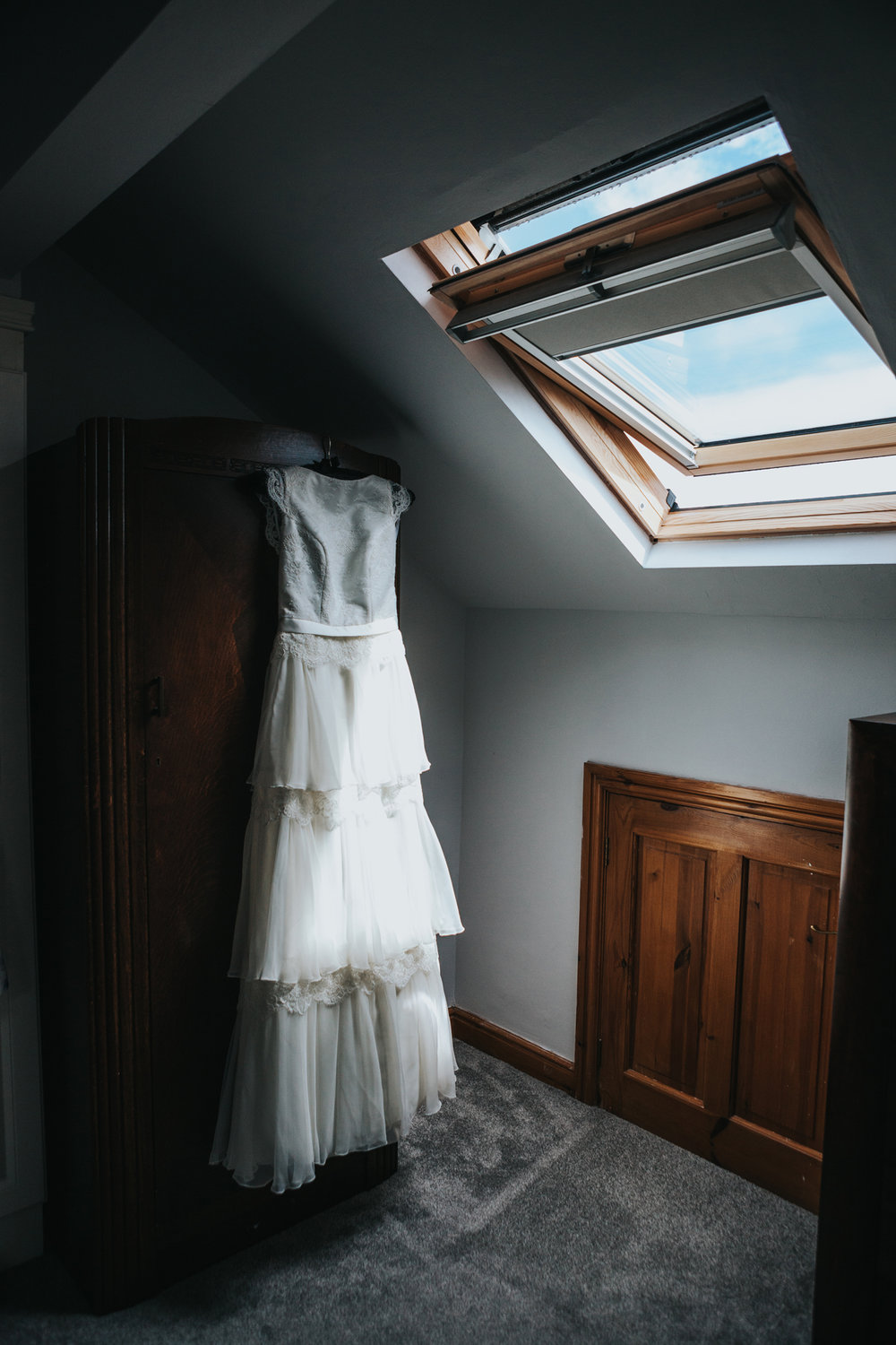 Brides dress hangs on wardrobe, Manchester.
