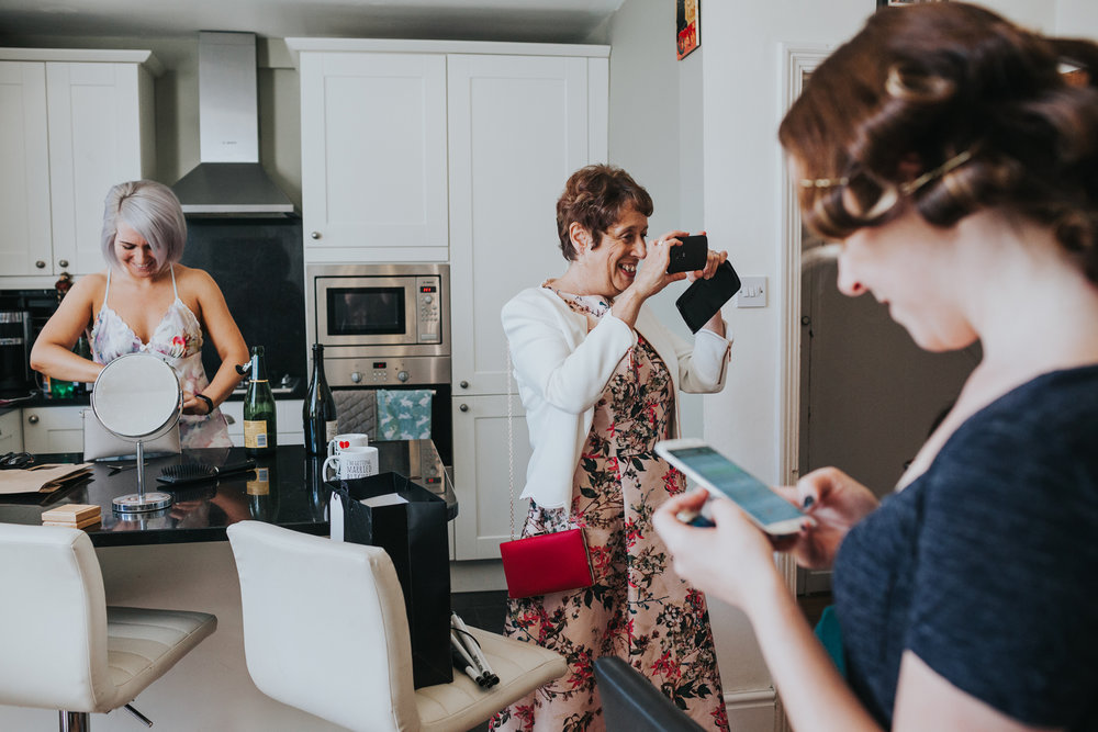 Bride, her mum and a bridesmaid hand out in the kitchen together taking photographs with their phones.
