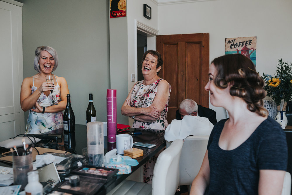 Bridal party laugh together in brides kitchen as she gets ready for her wedding.