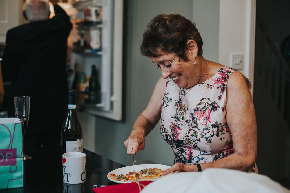 Mother of the bride cuts pizza for everyone.