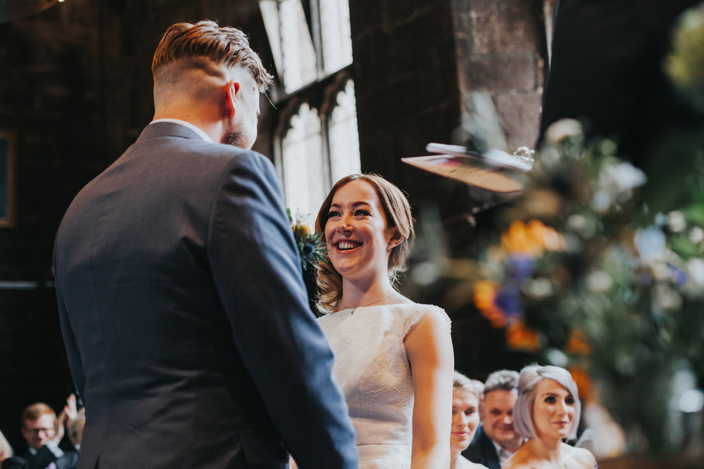 Bride looks at Groom, looking very happy at Chetham's Library Manchester