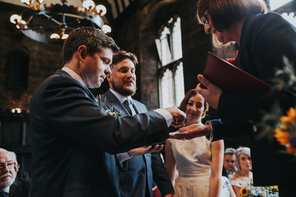 Best Man hands over the rings.