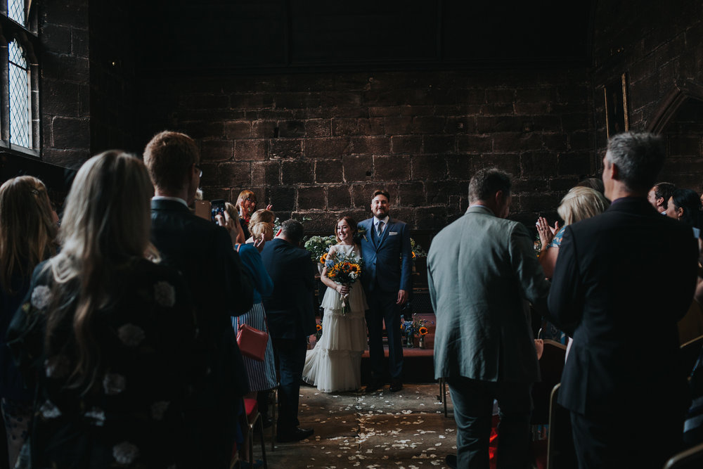 Bride and Groom stand married in front of their wedding guests at Chetham's Library Manchester.