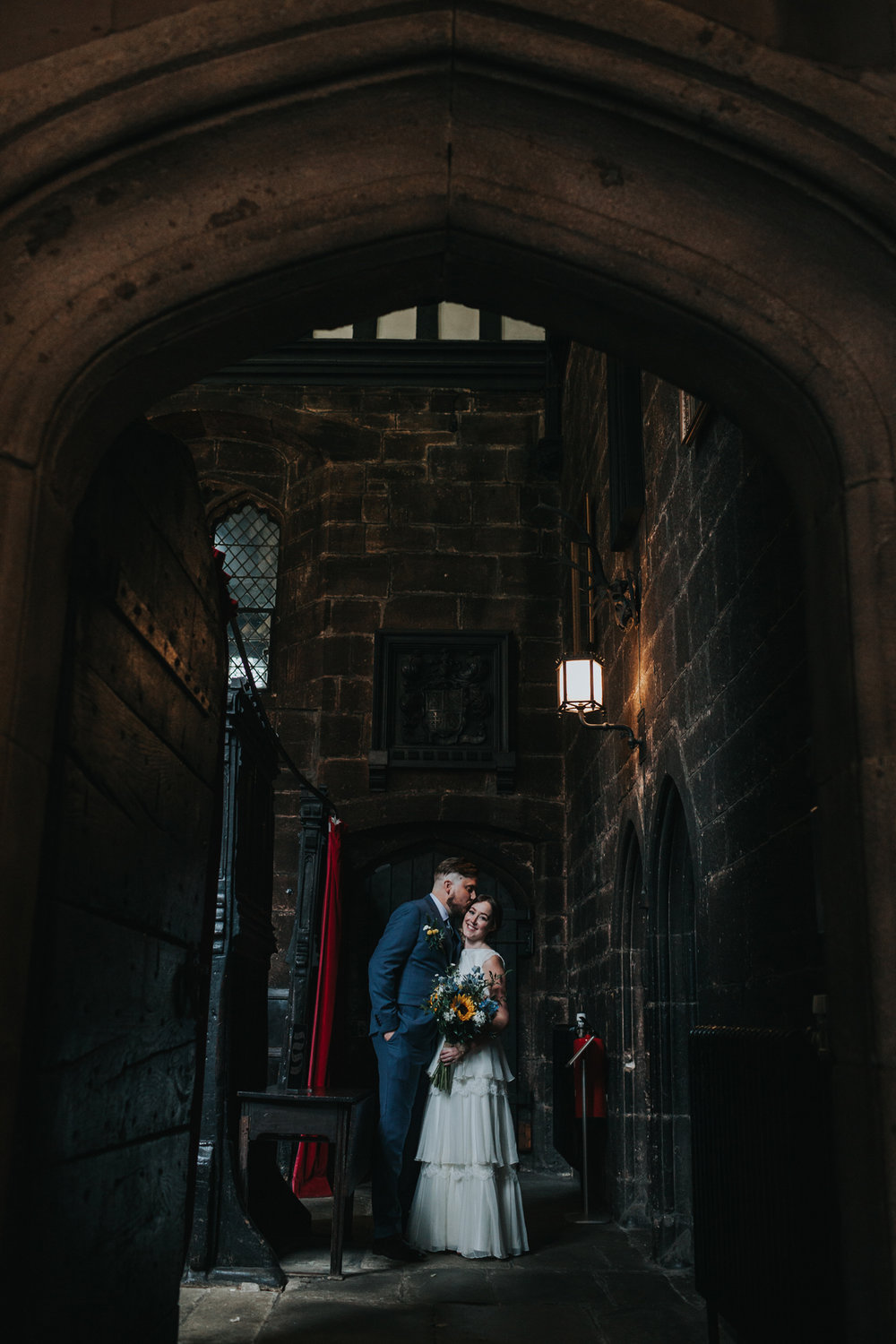 Bride and Groom have a moment in the doorway at Chetham Library Manchester.