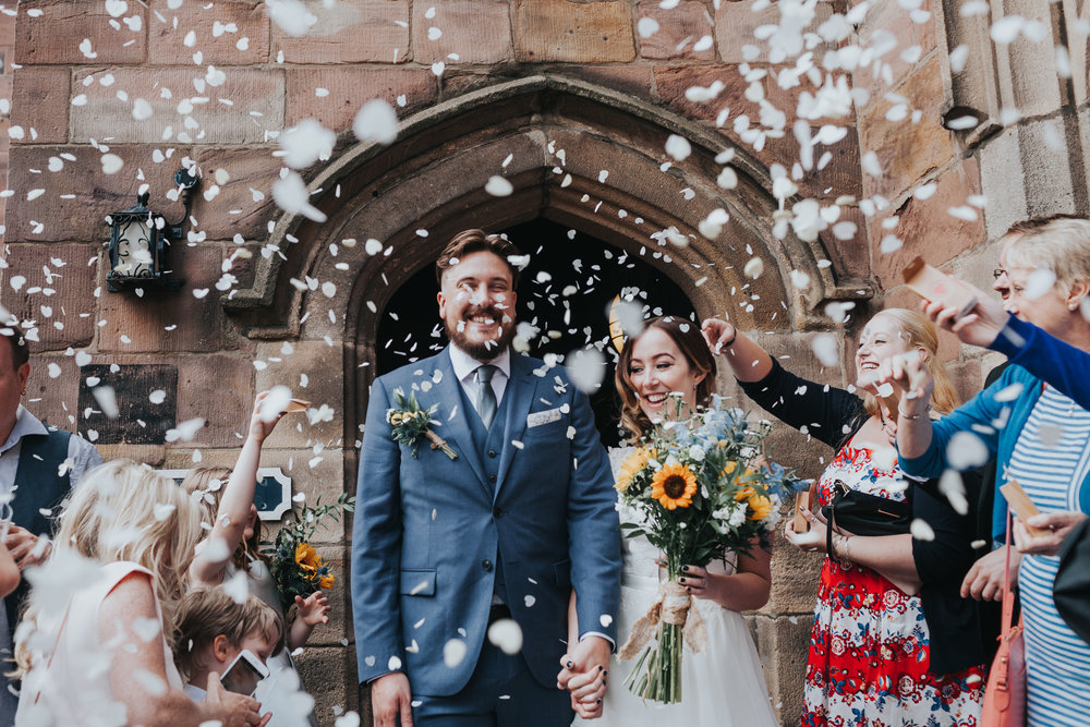 Bride and Groom have confetti thrown at them outside Chetham Library.